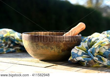 Tibetan Singing Bowl On A Table Outdoor. Translation Of Mantra Transform Your Impure Body, Speech An