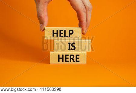 Help Is Here Symbol. Wooden Blocks With Words 'help Is Here' On Beautiful Orange Background. Busines