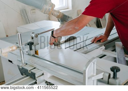 Work In The Furniture Shop. Furniture Production. A Man In A Red T-shirt Works Behind A Machine To P