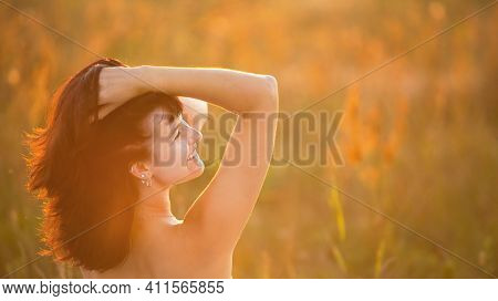 A Bare-shouldered Woman Holds Her Long Dark Hair In Her Hands In A Feminine Way, Happy In The Sunset