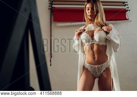 Beautiful Young Woman With Body In Lingerie Near A Mirror In A White Room.