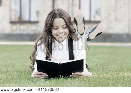 Basic Education. Adorable Little Girl Learn Reading. Schoolgirl School Uniform Laying On Lawn With F