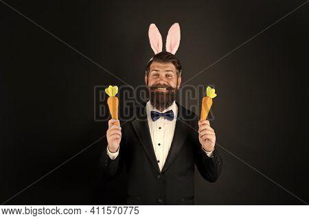 Something Truly Organic. Easter Bunny Bringing Organic Carrots. Happy Businessman Wear Rabiit Ears.
