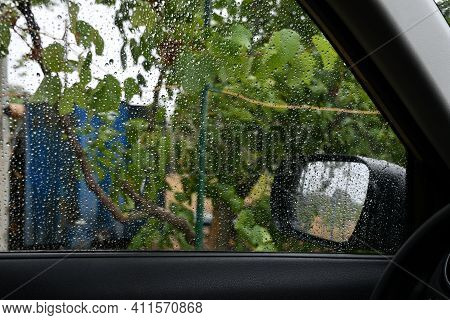 Texture Of Transparent Glass Covered With Shiny Blur Raindrops. Wet Side Window Shot Inside Car In R
