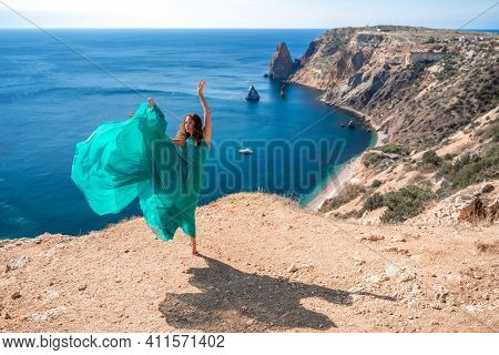 A Slender Girl In A Long Mint Dress Dances Barefoot Over The Beach With A View Of The Sea And Mounta