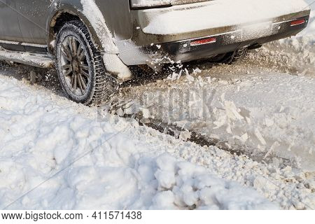 Road Snow Flies Up From A Vehicles Spinning Wheel. Cars Wheels Spin And Spew Up Pieces Of Snow It At