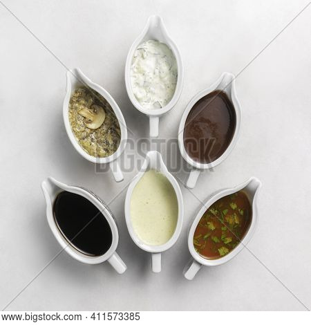A Set Of Several Different Oriental Sauces In Beautiful Ceramic Saucers On A White Marble Table. Ket