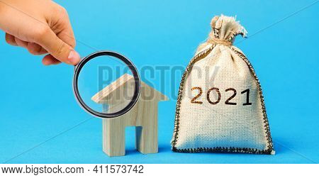Money Bag 2021 And A Wooden House. Real Estate Concept. Family Budget Planning. Investments, Plans,
