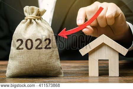 A Businessman Holds An Arrow Down Near The House And A 2022 Money Bag. Forecasting The Real Estate M