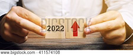Businessman Holds Wooden Blocks With The Inscription 2022 And An Up Arrow. The Forecast Concept For