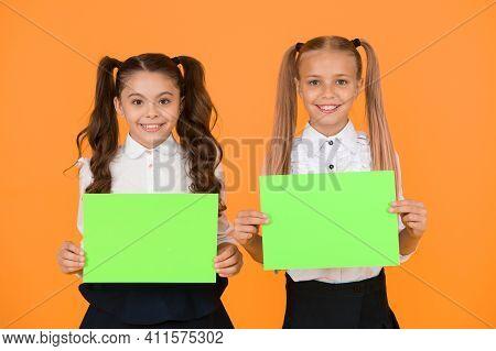 School Socialization. Girls School Uniform Hold Poster. Back To School Concept. Schoolgirls Show Pos
