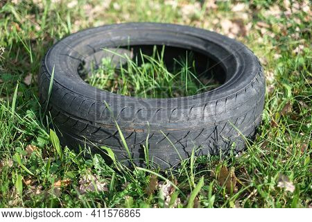 Old Used Rubber Car Tire Discarded On Raw Forest Ecosystem, Environmental Industrial Pollution