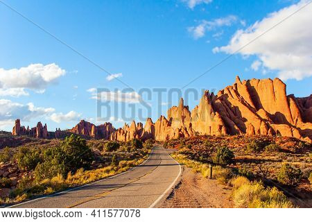 Asphalt road in the park. Arches Park in Utah, USA. Picturesque red-brown sandstone cliffs form a unique landscape. The unique beauty of Arches Park. Grandiose rock compositions natural origin