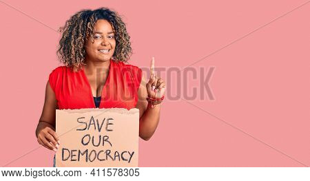 Young african american plus size woman holding save our democracy banner surprised with an idea or question pointing finger with happy face, number one