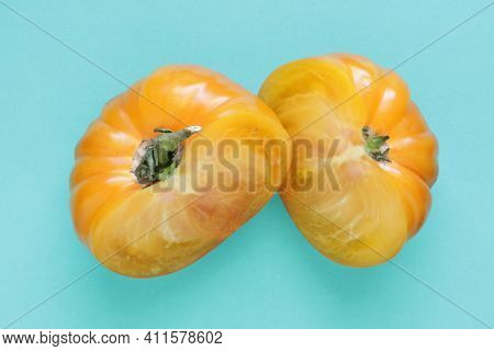 Yellow Heirloom Tomato Sliced In Half On Bright Blue Background.