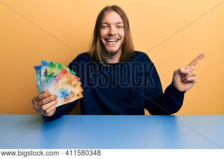 Handsome caucasian man with long hair holding swiss franc banknotes smiling happy pointing with hand and finger to the side