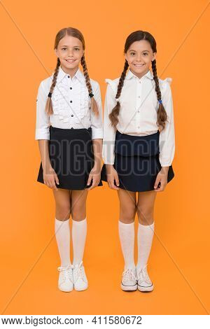 Making Everything Right. Excellent Pupils. Girls Perfect Uniform Outfit On Yellow Background. Accord
