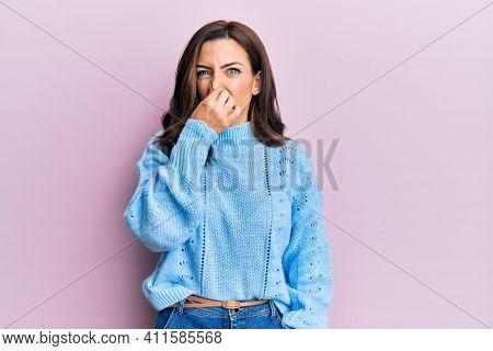 Young brunette woman wearing casual winter sweater over pink background smelling something stinky and disgusting, intolerable smell, holding breath with fingers on nose. bad smell