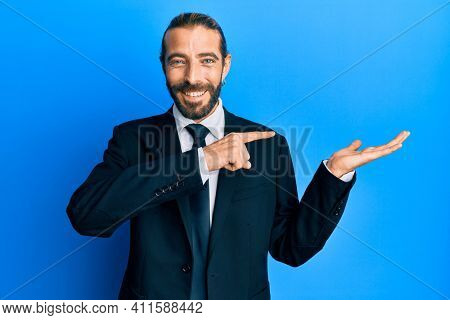 Attractive man with long hair and beard wearing business suit and tie amazed and smiling to the camera while presenting with hand and pointing with finger.