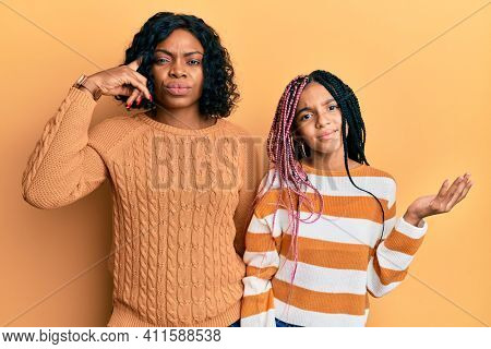 Beautiful african american mother and daughter wearing wool winter sweater confused and annoyed with open palm showing copy space and pointing finger to forehead. think about it.