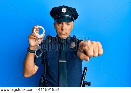 Handsome middle age mature man wearing police uniform holding metal handcuffs pointing with finger to the camera and to you, confident gesture looking serious
