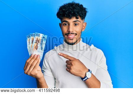 Young arab handsome man holding 100 swiss franc banknotes smiling happy pointing with hand and finger