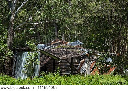 An Old Abandoned Shack Collapsing With Age And Decay Amongst The Trees