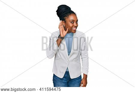 Young african american woman wearing business clothes smiling with hand over ear listening an hearing to rumor or gossip. deafness concept.