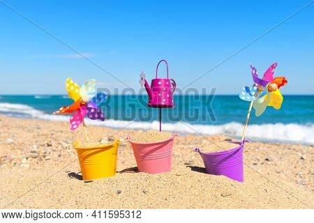 Colorful toy buckets and windmills at the beach