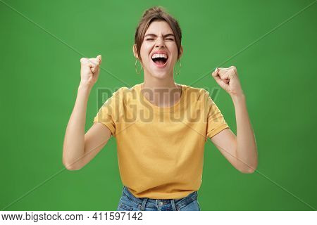Waist-up Shot Of Charismatic Energized And Excited Female In Yellow T-shirt Closing Eyes Yelling Fro