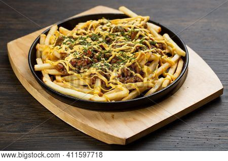 French Fries With Chopped Beef In A Metal Frying Pan On A Wooden Board. Fried Roll With Meat And Che