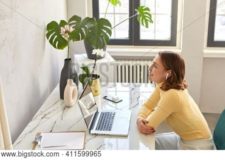 Side View Of Female In Wireless Earphones Sitting At Table With Netbook And Enjoying Music While Smi