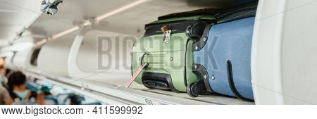 Carry-on luggages in overhead compartment of plane for international flights. Travel restrictions during coronavirus not allowing hand baggage inside airplane.