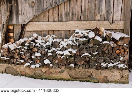 Woodpile Of Firewood On The Outskirts Of Farm, Yard And Winter Forest