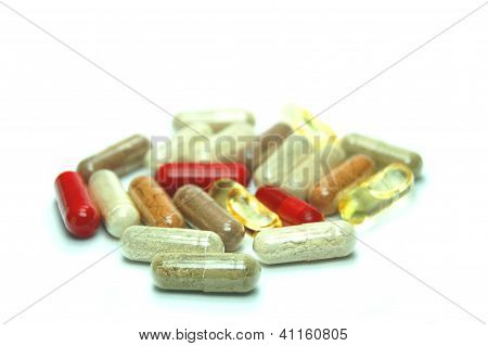 plenty of herbal capsules on white background