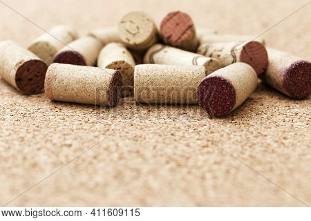 Corks From Wine Bottles Lie In A Pile On A Wooden Cork Background. Natural Wood Fon With Heap Of Cor