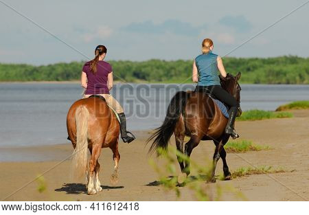 Two Women Are Riding On Horseback On Beach, Back View.