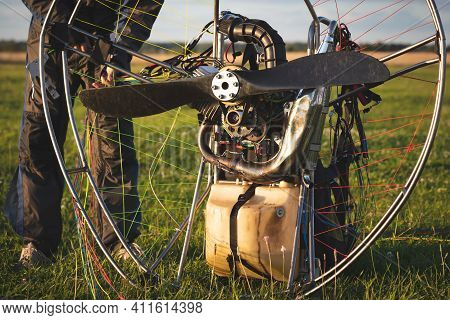 A Male Pilot Is Preparing A Gasoline-powered Paralet For Flights. Paragliding For Individual Paragli