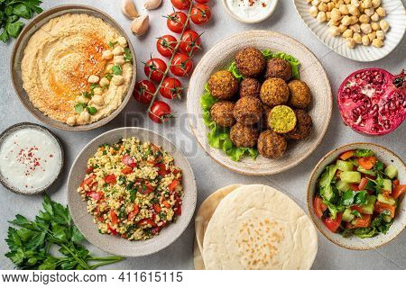 Middle Eastern Or Arabic Cuisines, Falafel, Hummus, Tabouleh, Pita And Vegetables On A Concrete Back