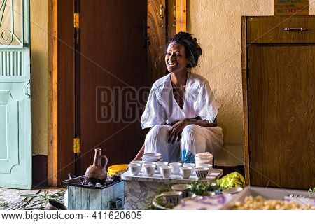 Axum, Ethiopia - Feb 09, 2020: Young Woman In Traditional Clothing Is Preparing A Coffee Ceremony. T