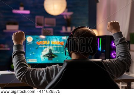 Excited Player With Headphones Making Winner Gesture While Playing Games On Computer At Gaming Home