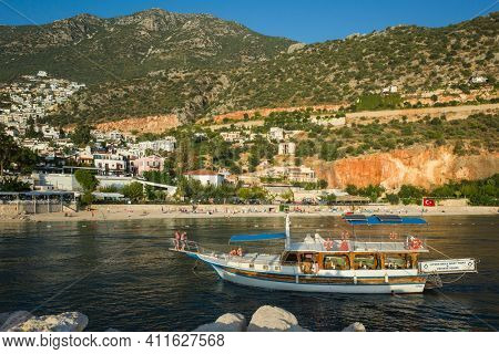Kalkan, Turkey - 12 October, 2019: Daily boat trip and privat tour boat with tourists in Kalkan marina with coastal town on hills, Popular tourist destination on Turkish Mediterranean coast