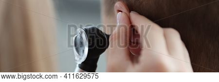 Otorhinolaryngologist Pulling Ear With His Hand And Looking At It With Otoscope Closeup. Otoscopy Co