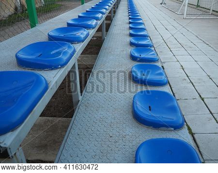 Seats And Benches On The Sports Ground. Plastic Blue Seats For Spectators And Fans, Empty, No People