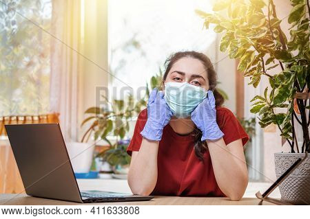 Coronavirus.a Young Woman In A Medical Mask And Gloves, Leaning On Her Hands With Boredom And Lookin