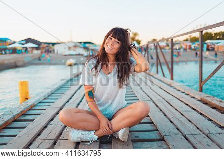 A Pretty Woman With A Tattoo On Her Arm, Smiling And Sitting Cross-legged On A Dock By The Sea. Conc