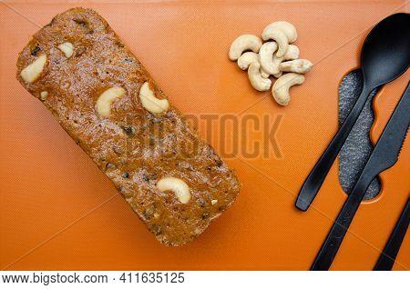 Homemade Rawa And Cashew Nuts Cake On Orange Coloured Chopping Board