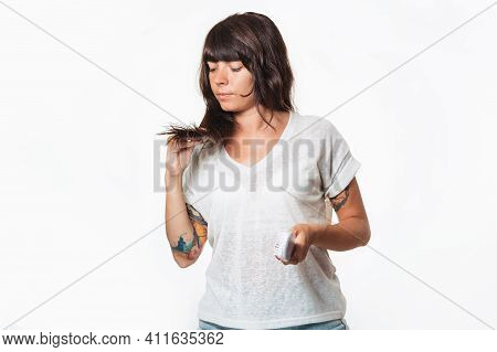 A Woman With A Tattoo On Her Arm Holds A Comb, And Examines The Tips Of Her Hair. Copy Space. White