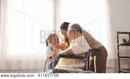 Happy Family Multi-generation Mother And Daughter Taking Care Of The Senior Granddfather In The Hous