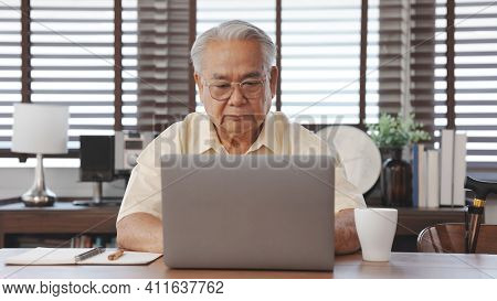 Happy Senior Male Using Laptop Searching For Health Insurance Online Website On Laptop Computer Buyi